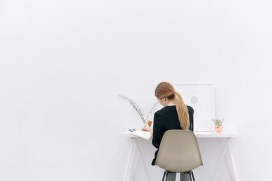 A woman sits at a desk writing a tender bid by www.naomiclewsconsultancy.com/freelancebidwritinguk.html